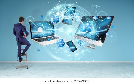 Tech devices connected to each other by businessman on office wall 3D rendering