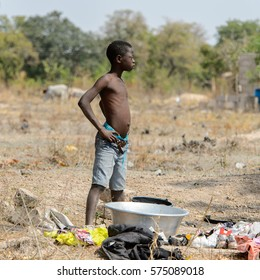 TECHIMAN, GHANA - JAN 15, 2017: Unidentified Ghanaian boy stands near basin on the Washing Day, which is every Sunday
