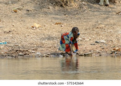TECHIMAN, GHANA - JAN 15, 2017: Unidentified Ghanaian little girl gets water with a bottle on the Washing Day, which is every Sunday