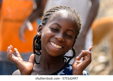 TECHIMAN, GHANA - JAN 15, 2017: Unidentified Ghanaian  girl in a dress with white stars smiles in a village. Ghana people suffer of poverty due to the bad economy