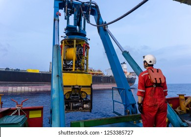 A techinician standing nearby Remoted Operated Vehicle (ROV) hanging on Launch & Recovery System (LARS) for underwater pipeline survey and inspection nearby Floating Storage Offloading (FSO) vessel.