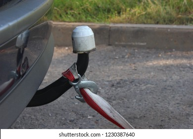 Technical assistance, car towing - tow rope with hook tied to the traction coupling device in the rear bumper, close up side view