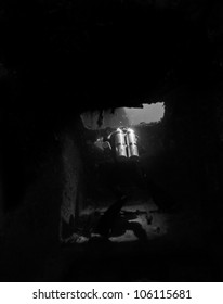 A technical diver in complete darkness outlined by a open doorway creating a shadow in a sunken shipwreck in the John Pennekamp State Park. The USCG Bibb in Key Largo, Florida.