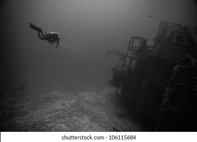 A technical diver swimming alongside of an underwater shipwreck laying on its side. The USCG Bibb is an artificial reef inside the John Pennekamp State Park in Key Largo, Florida.