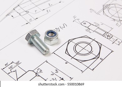 Technical drawings of bolts and nuts. Engineering, technology and metalworking. Metal bolt and nuts on printed drawings background.