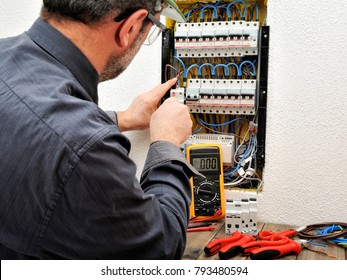 Technical electrician fixing the cable into the terminal of a circuit breaker of a residential electrical panel