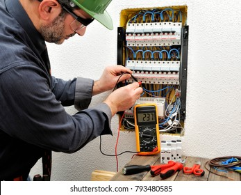 Technical electrician measures the voltage of a circuit breaker of a residential electrical panel