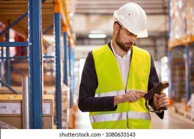 Technical equipment. Smart handsome man touching a scanner while using it for work in the storehouse