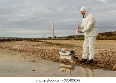 Technical expert, observes the tube containing polluted water. / Polluted Water Analysis. / Industrial district
