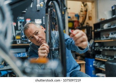 Technical expertise taking care Bicycle Shop. Repair technician bicycles was repaired gear bike shop. Friendly and competent bicycle mechanic in a workshop repairs a bike