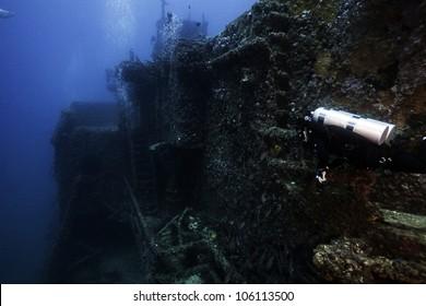 A technical female diver swimming alongside the USCG Duane. A sunken shipwreck in the John Pennekamp State Park in Key Largo, Florida.