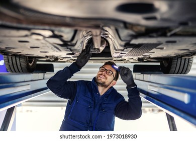 Technical inspection of the car. Car service in the workshop. A man in a blue uniform stands under a car in the garage and checks the car's axles. It illuminates the chassis with a flashlight