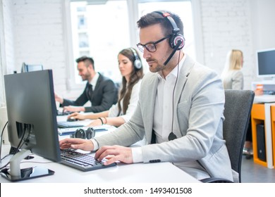 Technical support dispatcher man using computer at his workplace in call center