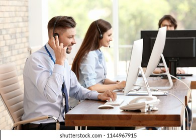 Technical support operators with headsets at workplace