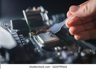 Technical support worker greases with thermal grease paste computer processor. Thermal compound on on PC CPU. Cooling upgrade concept.
