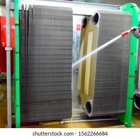 Technical worker cleaning Heat exchanger plate of the water cooling system on power plant.