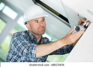 technician adjusting cctv camera on wall