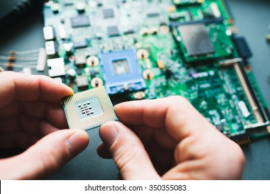 Technician analysis and plug in CPU microprocessor to motherboard socket. Workshop background
