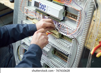 Technician assembling low voltage assembling industrial controlpanel in workshop. Close-up photo of the hands.