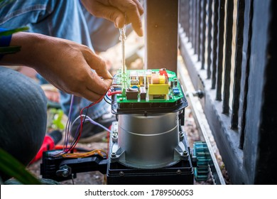 A Technician assembling motor system and testing motor automatic gate by screwdriver home security system.
