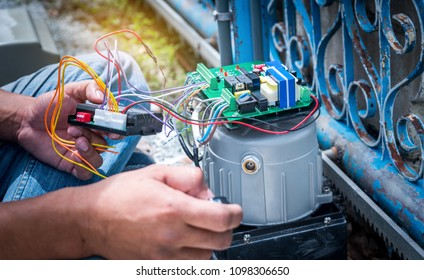 Technician assembling and testing motor automatic gate home security system