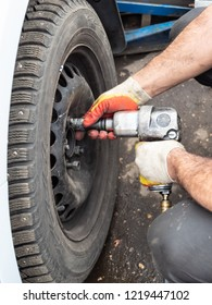 technician attaches a winter car wheel by pneumatic torque wrench outdoors during seasonal replacement of tires