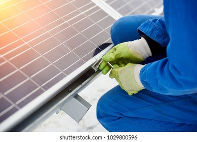 Technician in blue suit installing blue solar panels with screw. Photovoltaic modules as renewable energy source. Alternative energy production innovation ecological sustainable resources