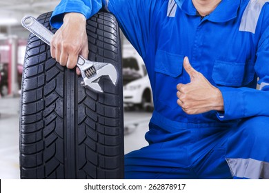 Technician with a blue workwear, holding a wrench and a tire while showing thumb up