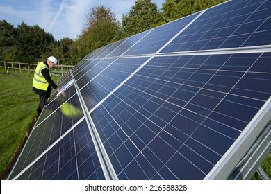Technician with blueprints standing near large solar panels