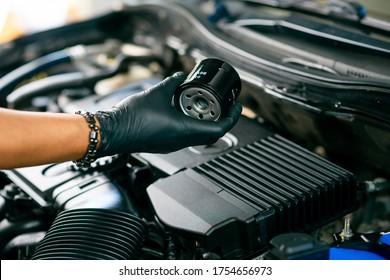 Technician change car oil filter, automotive spare part. Car maintenance concept.