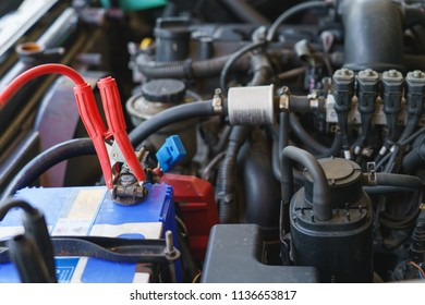 Technician check car system. Mechanic using battery jumper cables to charging battery in car garage.