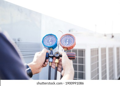 Technician is checking air conditioner ,measuring equipment for filling air conditioners.Cooling system