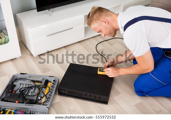 Technician Checking Broken Amplifier With Digital Multimeter