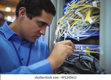 Technician checking cables in a rack mounted server in server room