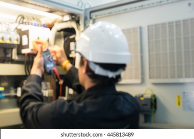 Technician is checking voltage or current in control panel of power plant