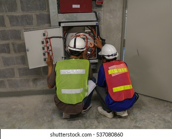 Technician checking wiring of control panel