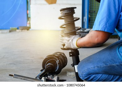 Technician checkup spring and shock absorber to repair car suspension.