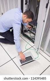 Technician connecting his laptop to server in data center