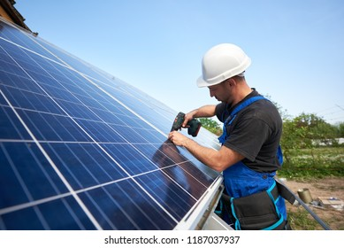 Technician connecting solar panel to metal platform using electrical screwdriver on blue sky copy space background. Stand-alone solar system installation, efficiency and professionalism concept.
