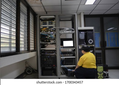 Technician was crouched down near computer racks. Engineer installs new server in the server room.