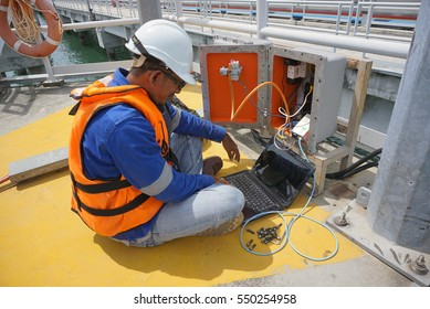 A technician doing maintenance work by using a laptop at a jetty.