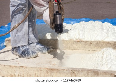 Technician dressed in a protective white uniform spraying foam insulation using Plural Component Spray Gun. Spraying polyurethane foam for roof and energy saving
