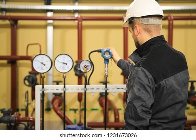 technician engineer checking pressure sensors manometers and monitoring data on gas industrial station