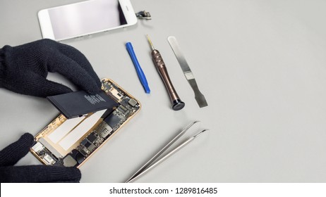 Technician or engineer disassembling components broken smartphone and take off battery for repair or replace new smartphone battery on desk with copy space