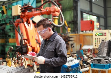 Technician engineer holding a notepad with robot machine in the background
