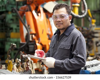 Technician  engineer holding a notepad with robot machine on background