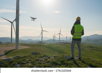 Technician Engineer in Wind Turbine Power Generator Station launches a drone for visual control of generators