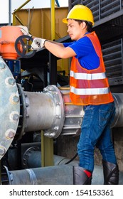 technician or engineer working on a valve on building technical equipment or industrial site in factory or utility