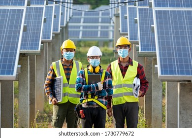 Technician and Engineer working in Solar cell Farm through field of solar panels checking the panels at solar energy installation.