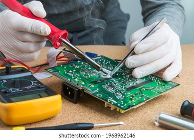 Technician engineer in workshop. He takes tin with a soldering iron and puts it on microcircuit.  Repairman in gloves is soldering circuit board of electronic device.